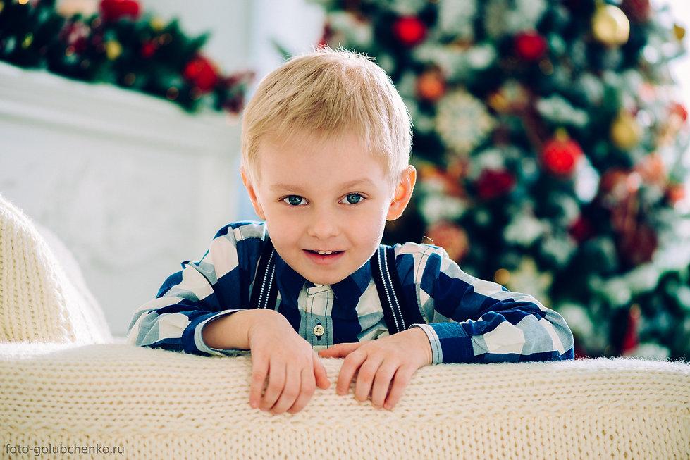 Детская фотосессия в студии.  Мальчик с открытым озорным взглядом смотрит в объектив.