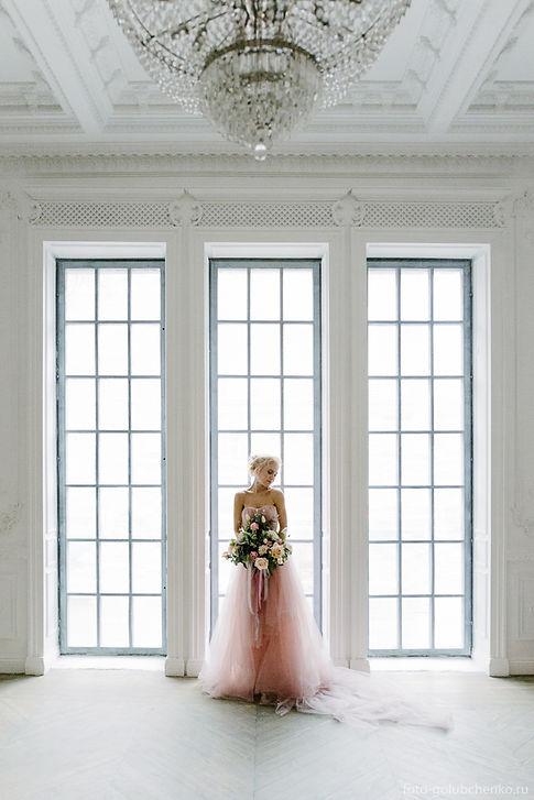 Девушка в свадебном платье на фоне витража. Она похожа на хрустальную статуэтку на фоне просторного интерьера в классическом стиле.