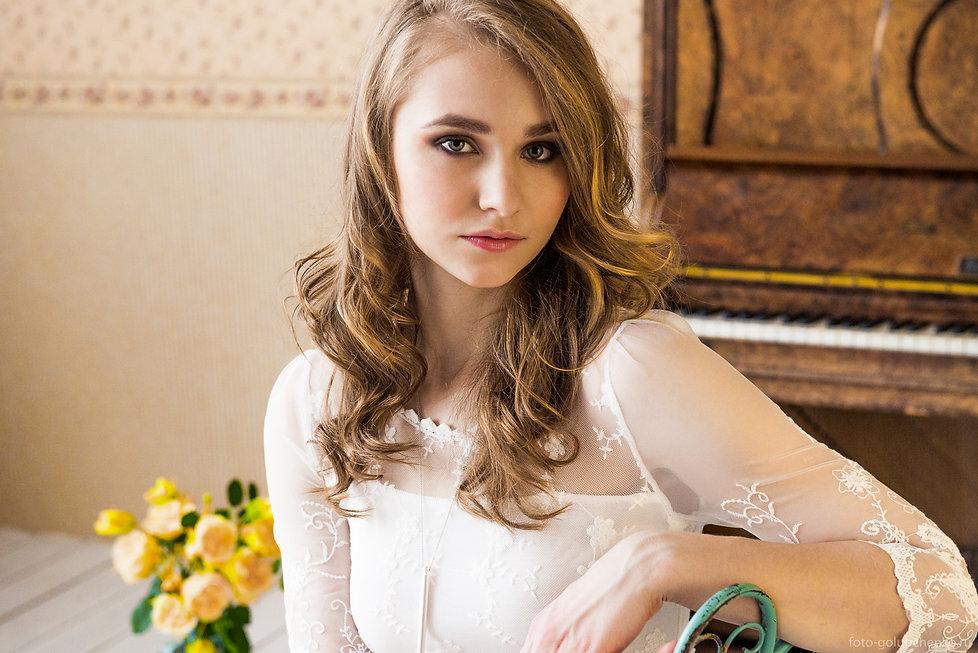 Портрет модели в интерьере с пианино. Коричневый преобладающий тон и красочный бутоны наполняют атмосферу женским теплом и уютом.