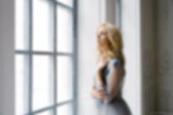 Милая блондинка в будуарном наряде у окна. Радостные мгновения предсвадебного ощущения. Мягкий утренний свет освещает нежную кожу девушки.