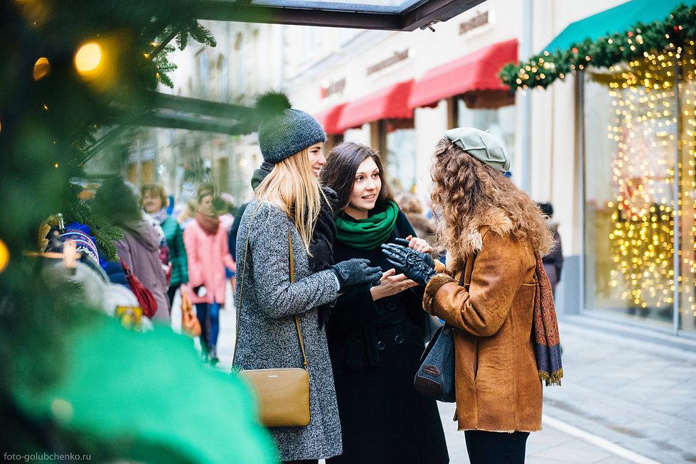 Встреча лучших друзей в новогодней Москве. Яркие огни украшают улицу.