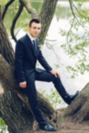 Фотография жениха на фоне озера. Темно - синий костюм хорошо, на контрасте, сочетается с оттенками природы.