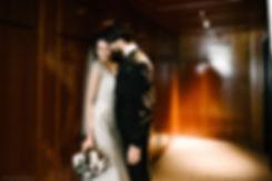 Нежное и страстное фото молодоженов в темном коридоре дорого отеля. Неяркий свет освещает контур их тел, подчеркивая позу и настроение