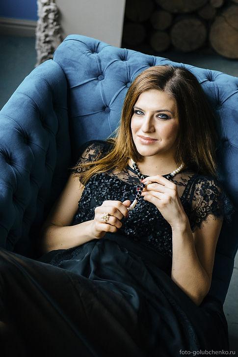 Фотосессия в студии. Эффектная молодая женщина лежащая на гостином диванчике.