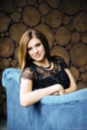 Молодая женщина облокотившаяся на спинку дивана в красивом узорном черном платье.