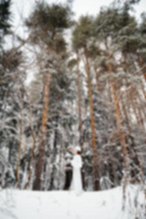 Молодой человек что-то нашептывает своей возлюбленной. Вместе они счастливы уединившись среди заснеженных деревьев.