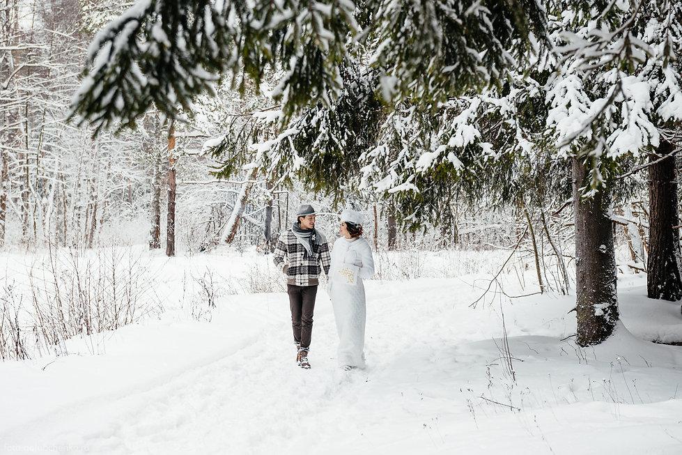 Предсвадебная прогулка в заснеженном лесу. Молодожены счастливы вместе, им есть о чем друг с другом поговорить.
