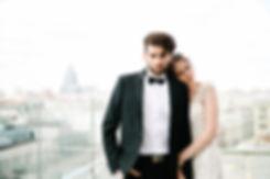 Стильно выглядящие жених и невеста позируют на фоне городского пейзажа