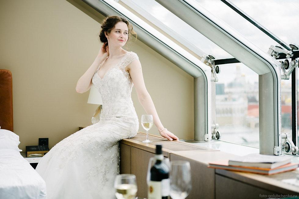 Элегантная невеста наблюдает великолепный вид из окна.