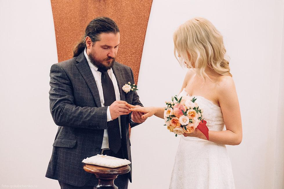 Аккуратные руки суженой старательно надевают кольцо на безымянный палец своему будущему мужу.  Элегантный букет придает торжеству ощущение праздника.