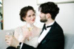 Влюбленные сидят с бокалами с шампанским и смотрят друг на друга