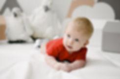 Лучезарный мальчик лежит на белом одеяле в яркой маечке. Красный является центральным акцентом в окружающем минимализме.