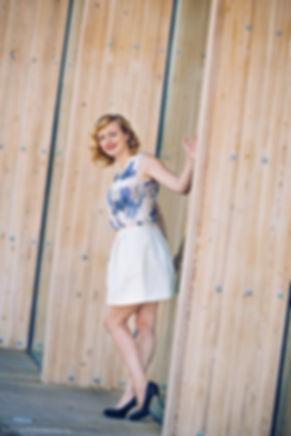 Динамичный снимок среди элементов архитектуры.  Одежда по цвету гармонично сочетается с деревянными пилонами здания.