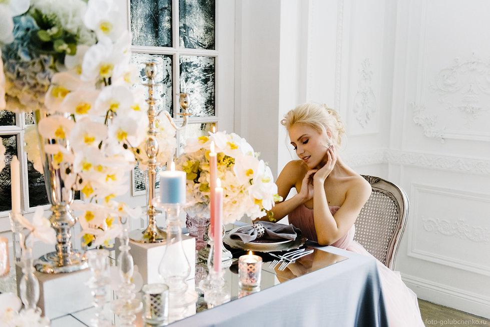 Портрет невесты, сидящей за изящно оформленным свадебным столом и ожидающей своего любимого. Теплый свет свечей передает атмосферу нежности и уюта.