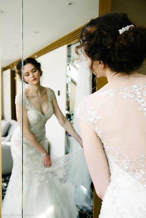 Невеста расправляет подол наряда у зеркала. Он выглядит превосходно.