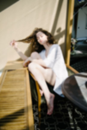 Красотка сидит в белоснежной тунике у окна и нежится в лучах восходящего солнца.