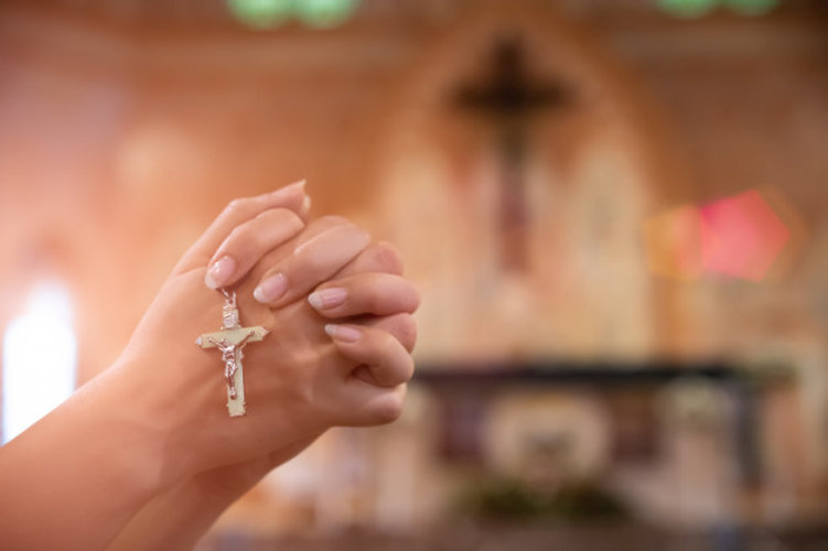 woman-hand-holding-rosary-against-cross-