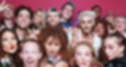 A group of people in 80 outfits are havng fun posing for a group picture