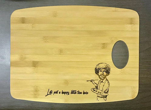 """Lets put a happy little tree here"" Cutting Board"