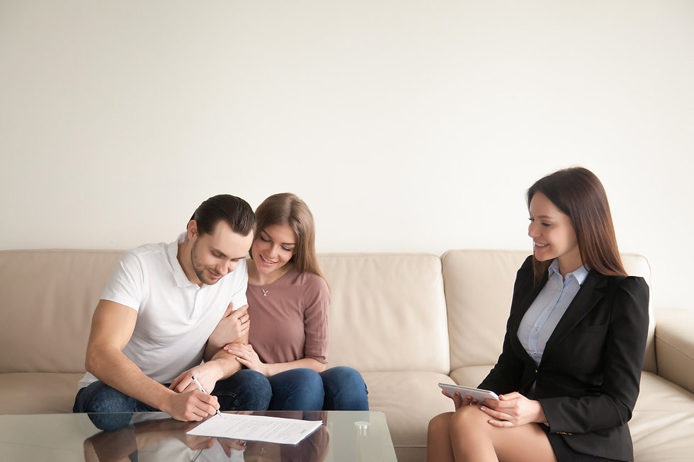 young-man-signing-papers-sitting-wife-re