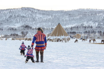 Sami family walking to reindeer camp