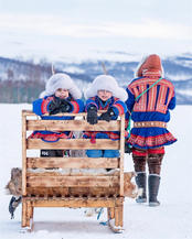 Sami family on a reindeer sleigh