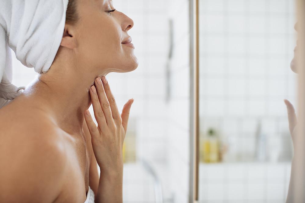 Woman using treatment to moisturise her skin