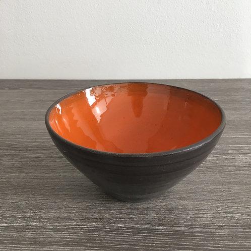 Skål i sort ler med orange glasur