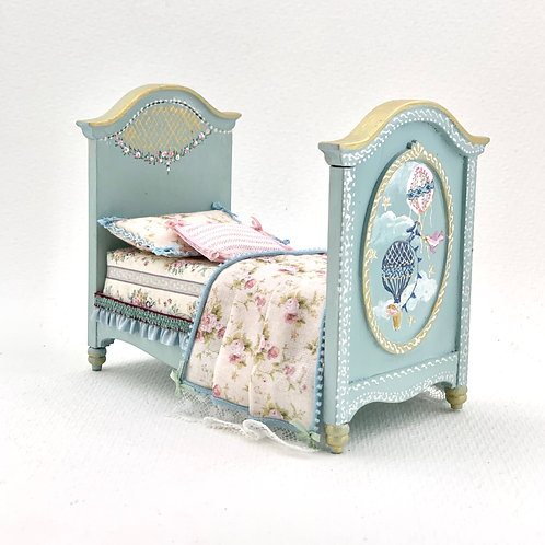 Child's cot painted by hand in blue tones with motifs of air balloons painted on