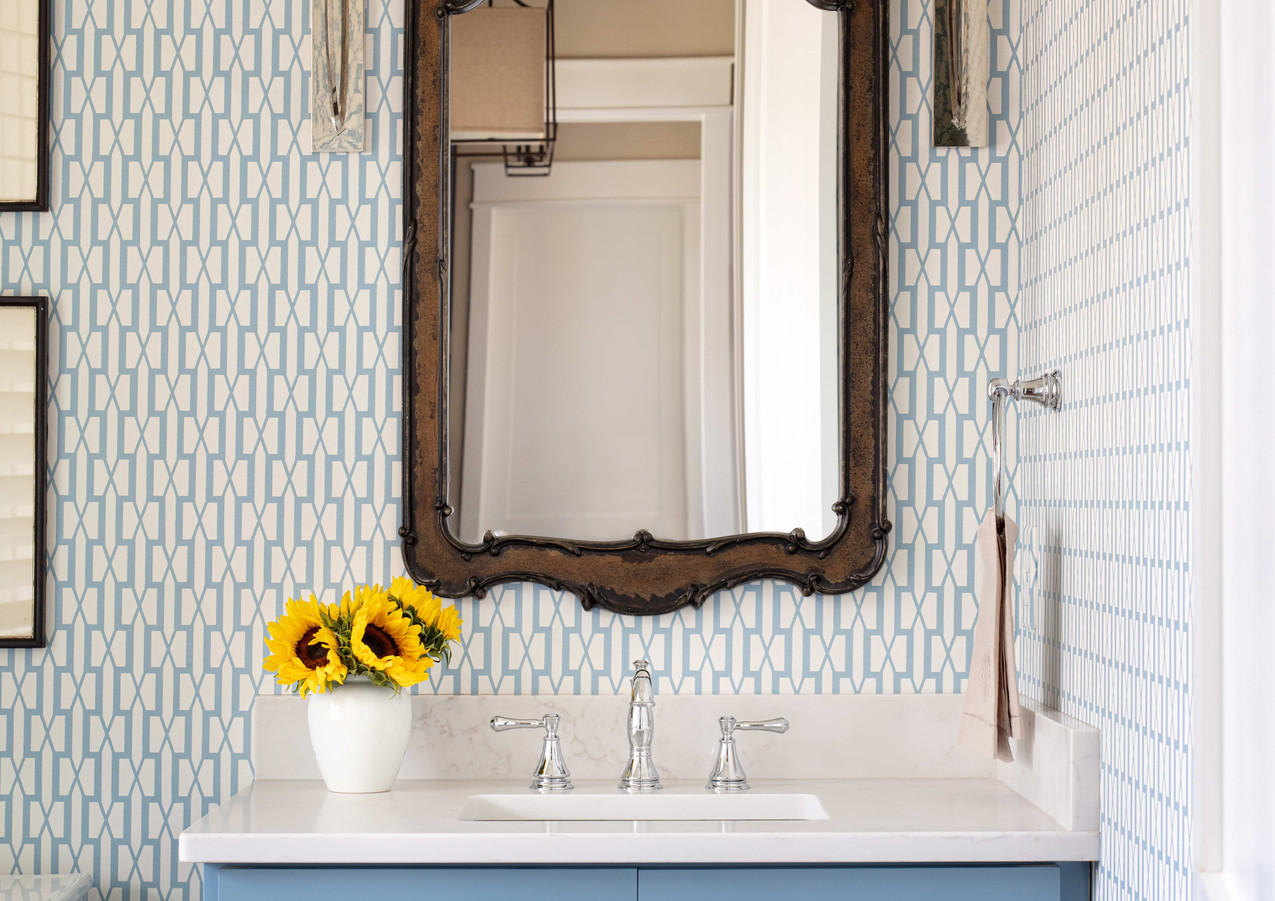 The guest powder is a little preppier--the graphic pop of the wallcovering is perfect!