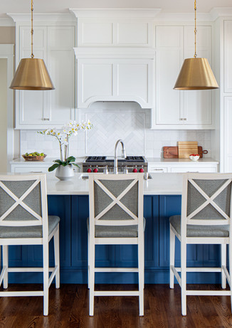 A classic kitchen with pops of blue and brass keeps things interesting. Performance fabric on the barstools means they stand up to the grandkids.