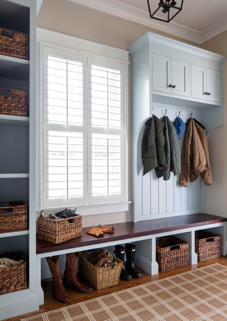 A mudroom in a cheerful, but restrained, blue provides a place for everything as you enter from the garage.