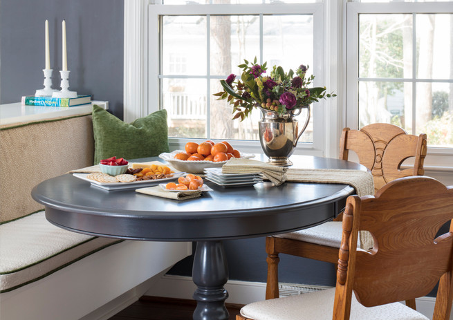 A built-in banquette features cabinetry on the backside to provide the formal dining area easy access to servingware, napkins, etc. This breakfast banquette is part of the eat-in kitchen.