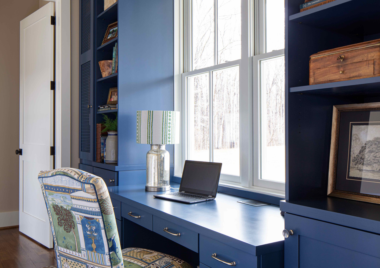 We used the passthrough to the main bedroom suite to house a very functional pocket office. The custom cabinetry features hidden wireless charging and pop up power outlets, while the towers hide all the less-pretty items like a printer and file storage.