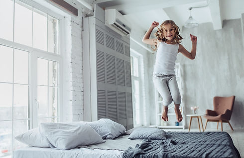A young girl jumping on a Luxurious, Comfortable Bed