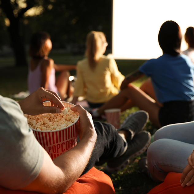 Young people with popcorn watching movie