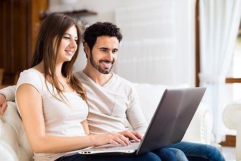 Portrait of an happy couple using a lapt