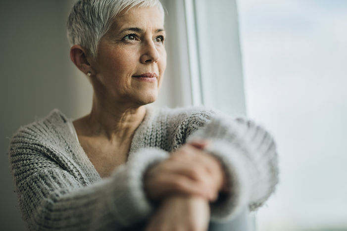Mature Woman Looking Out Window - iStock