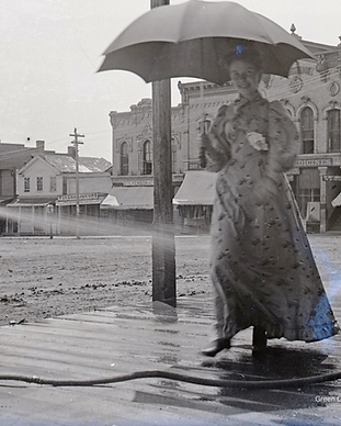 historic black and white photo of woman on wood sidewalk