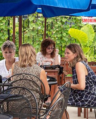 women eating outside a restaurant