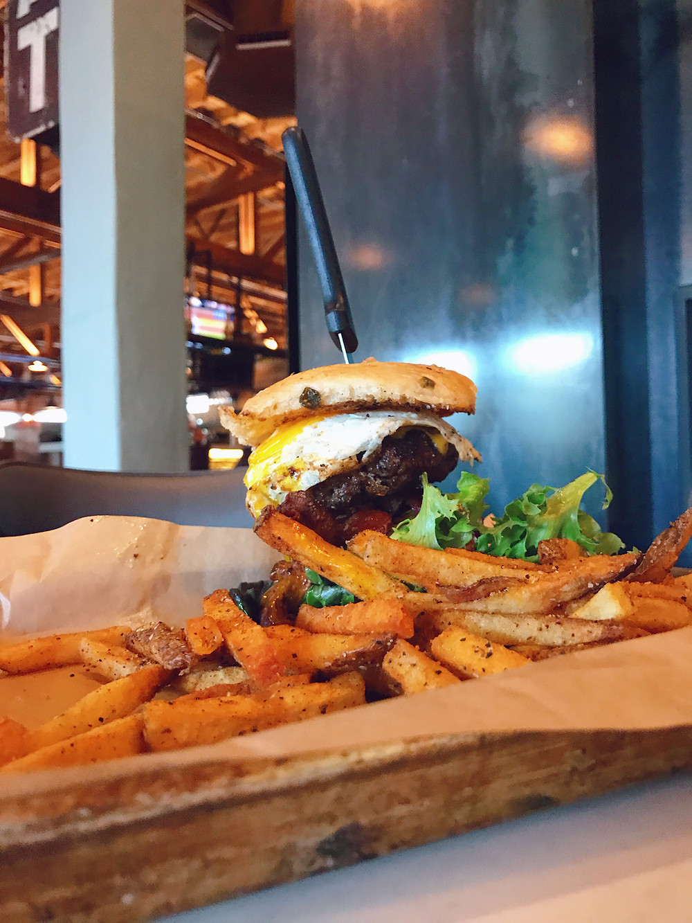 The Downtown Socials Kitchen Sink meal, the photo shows the burger with a knife sticking out of the top of it, surrounded by French fries