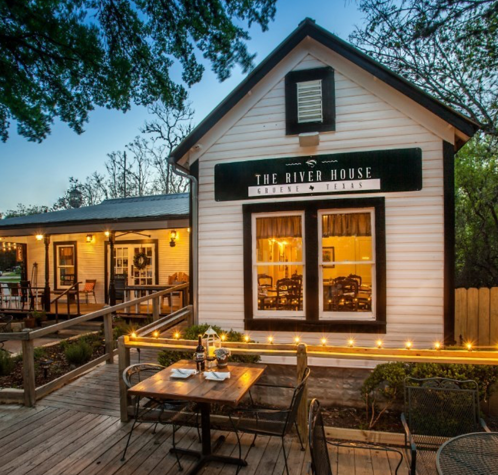 image depicts the river house restaurant at dusk, with lights on in the interior and the sun setting behind; The River House NB TX restaurant, gruene texas restaurants, Hill Country Restaurants, Top ten restaurants in Gruene