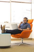man-wearing-headphones-sitting-on-orange
