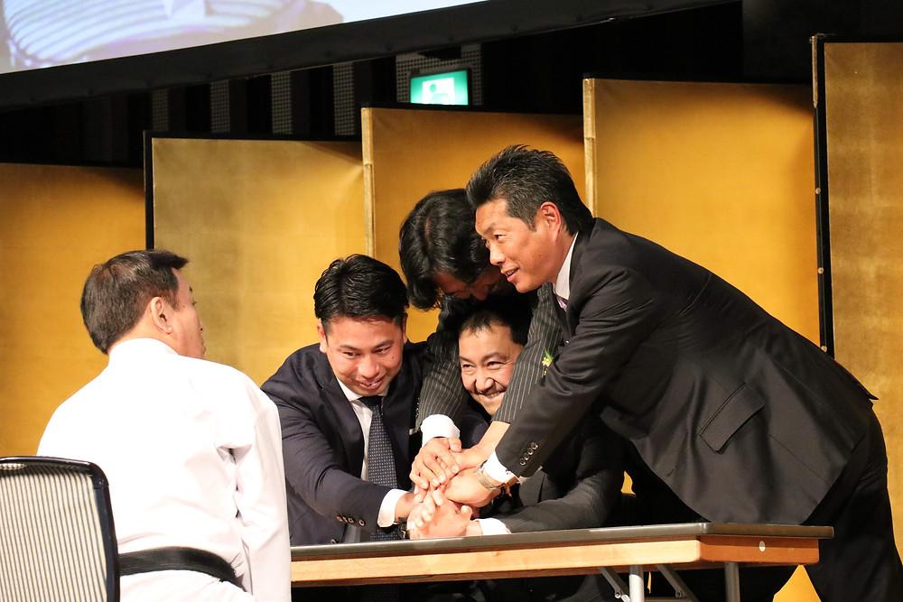 手を組まず、気による腕相撲を披露する塾長