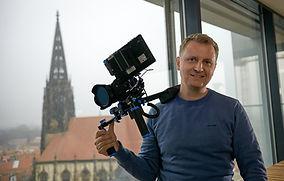 Portrait_Simon_Jöcker_mit_Kamera.jpg