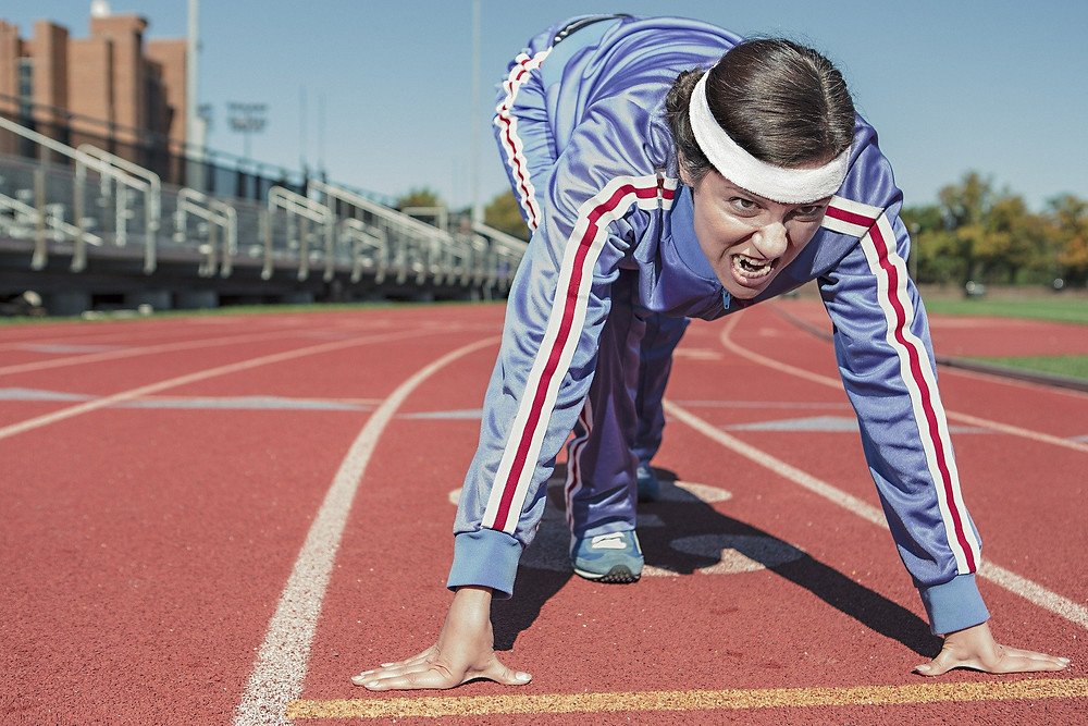 A runner, crouched with an aggressive, fierce expression is crouched, ready to sprint off the blocks on an outdoor track
