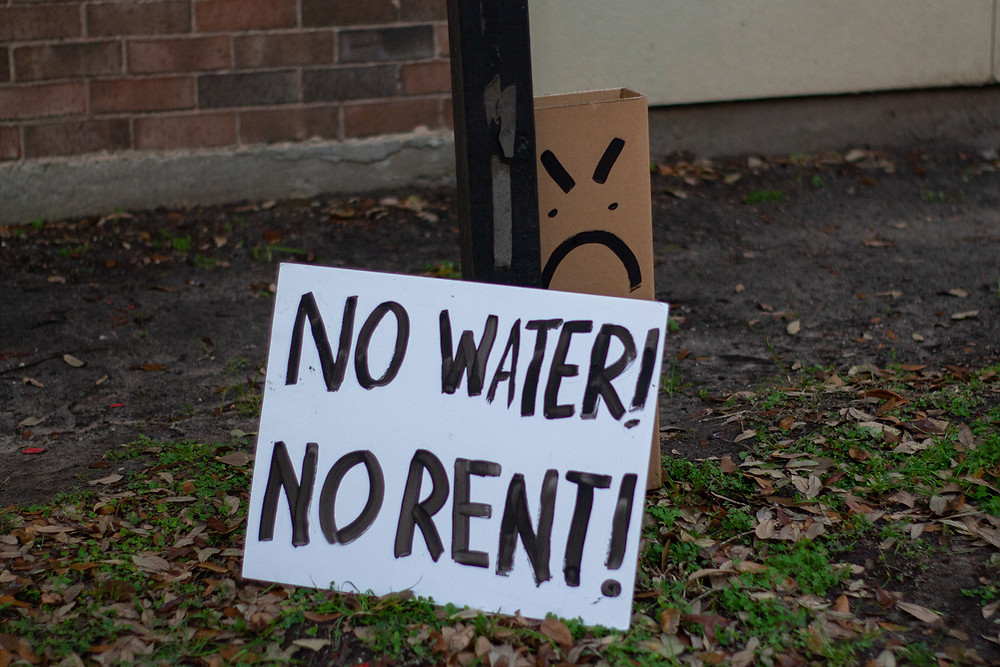"""A sign that says """"No Water, No Rent!"""""""