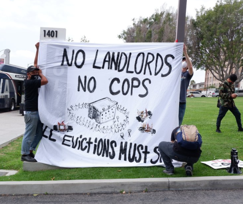 Tenant unionists in LA cover the local police precinct's sign with a message of their own