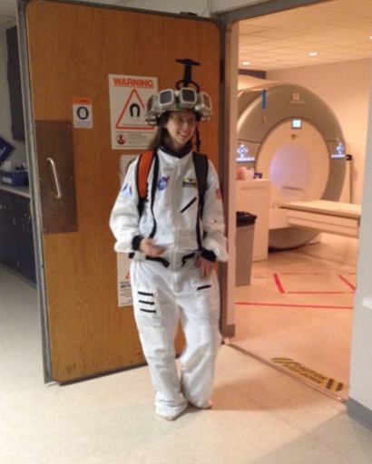 Julie Brefczynski-Lewis wearing a mock-up AMPET helmet while standing in front of a traditional PET scan machine. Courtesy of Julie Brefczynski-Lewis/WVU.