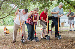 The senior pastor and church leadership lean onto shovels during a ceremonial groundbreaking on the